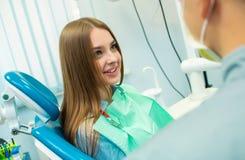 Een mooi meisje zit als tandvoorzitter en bekijkt een mens arts die aan haar spreekt stock fotografie