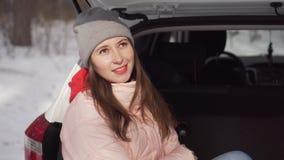 Een mooi meisje zit in auto op ijzige de winterdag vindt koud het bos bewondert stock footage