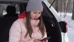 Een mooi meisje zit in de winterbos en met een glimlach die het nieuws doorbladeren stock footage