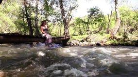 Een mooi meisje zit op brug het spelen met haar benen Er is een rivier onder de brug stock video
