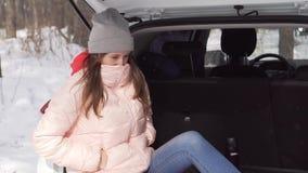 Een mooi meisje zit in een witte auto verwarmt haar handen met adem, rond kijkt stock video