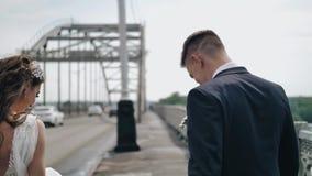 Een mooi paar in liefde loopt over de brug en heeft pret die rond op camera voor de gek houden stock video