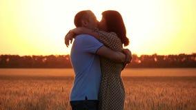 Een mooi paar in liefde op een tarwegebied bij zonsondergang De vrouwenlooppas aan de man kussen en omhelst hem Gelukkige Familie stock video