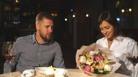 Een mooi paar in liefde ruilt giften voor de dag van Valentine ` s, een datum in een koffie stock video