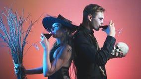 Een mooi paar, een man en een vrouw in heks en zombiekostuums Halloween die, 4k, het slow-moving schieten, glazen houden stock footage