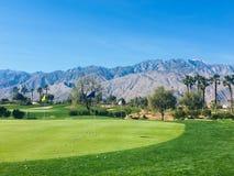 Een mooi praktijkgebied in Palm Springs, Californië, Verenigde Staten De groene scherf heeft een bos van golfballen door het gat stock foto