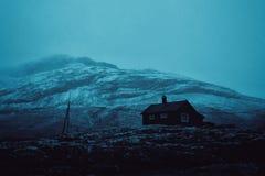 Een mooi schot van een huis op een heuvel met verbazende berg op de achtergrond stock fotografie