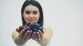Een mooi slank meisje eet gezonde vruchten Tijdens dit, neemt een vrij jonge vrouw een rijp druivenboeket omhoog in haar handen t stock video