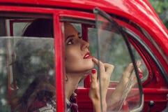 Een mooi speld-omhooggaand meisje in een plaidoverhemd verbetert samenstelling in de salon van een oude rode retro auto stock afbeeldingen