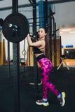 Een mooi sportenmeisje leidt een bicep met een staaf in haar op indient de gymnastiek royalty-vrije stock foto