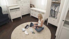 Een mooi zwanger blonde zit op het tapijt in de baby'sruimte De Baby'skleren zijn op de vloer rond haar stock videobeelden