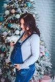 Een mooi zwanger jong meisje in een blauwe denimoverall houdt een beer in haar handen en bekijkt hem stock foto