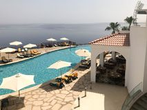 Een mooi zwembad met duidelijk water met zonparaplu's van de zon in een hotel in een tropische exotische toevlucht, een kuuroord  Royalty-vrije Stock Foto's