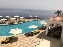 Een mooi zwembad met duidelijk water met zonparaplu's van de zon in een hotel in een tropische exotische toevlucht, een kuuroord  Stock Afbeeldingen