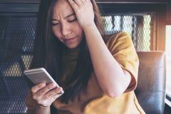 Een mooie Aziatische vrouw die slimme telefoon met het voelen van spanning bekijken royalty-vrije stock foto's