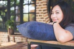 Een mooie Aziatische vrouw zit met kin die op haar handen boven een blauw hoofdkussen met gelukkig voelen rusten en ontspant in k stock fotografie