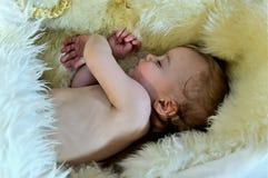 Een mooie baby die op een bontdeken legt Royalty-vrije Stock Foto