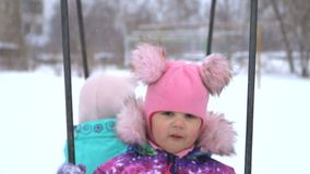 Een mooie baby die op een schommeling en het spreken slingeren Sneeuw witte achtergrond stock footage