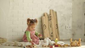 Een mooie babyspelen op de vloer met houten kubussen Onderwijs Speelgoed Peuteronderwijs kleuterschool stock video