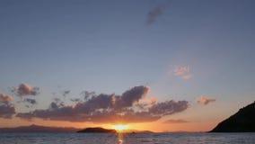 Een mooie blauwe hemel, de zon daalt in het overzees van achter de wolken en de eilanden stock videobeelden