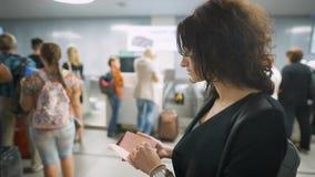 Een mooie dame controleert haar paspoort vóór de reis stock videobeelden