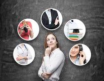 Een mooie dame in een formeel overhemd denkt over verschillende beroepen Zwart bord als achtergrond stock afbeelding