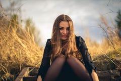 Een mooie donkerbruine meisjeszitting op treden De herfst Kunstfoto stock foto
