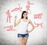 Een mooie donkerbruine vrouw in een wit mouwloos onderhemd en denimborrels dat op haar vinger omhoog wijzen De rode crossfitpicto Royalty-vrije Stock Foto's