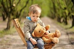 Een mooie, droevige jongenszitting op de stoel met teddybeer bij de lente Hazel boom royalty-vrije stock afbeelding