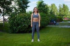 Een mooie dunne vrouwensportvrouw die hurkzit doen royalty-vrije stock foto's