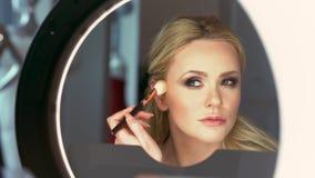Een mooie elegante blondevrouw maakt zich een betoverende avondmake-up bij de spiegel stock video