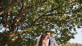 Een mooie en gelukkige bruid en een bruidegom onder de takken van een boom samen Verzacht aanraking van de handen Kus Ik houd van stock video