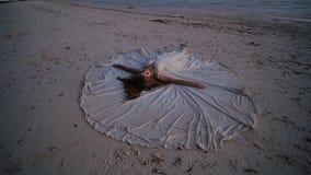 Een mooie en gelukkige bruid ligt op het zand tijdens zonsondergang, die een huwelijkskleding uitspreiden rond haar Het originele stock video