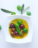 In een mooie fles, gekleed met kruiden Gemengde gemarineerde olijven in ceramische kom Royalty-vrije Stock Foto's