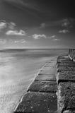 Overzeese treden in contact met het zeewater in zwart-wit Stock Foto's