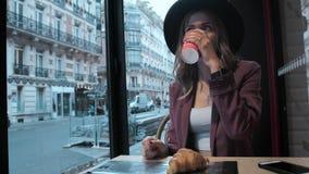 Een mooie Franse bedrijfsvrouw met een hoed drinkt koffie in een koffiewinkel tegen een achtergrond van een Franse straat stock video