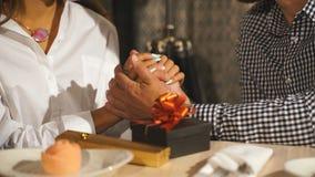 Een mooie gebaarde mens geeft een gift aan zijn meisje in een restaurant stock footage