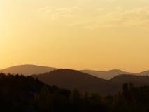 Een mooie gele zonsondergang op een verbazingwekkende berg Stock Foto's