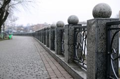 Een mooie granietomheining met gesmede metaalsecties en decoratieve ballen als decoratie De omheining wordt gebouwd langs de dijk royalty-vrije stock fotografie