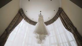 Een mooie huwelijks witte kleding die in een ruimte dichtbij een groot venster hangen stock video