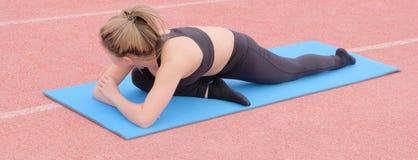 Een mooie jonge Aziatische vrouw die een oefening doen om de spieren van haar benen op een blauwe rubbermat te versterken Uitrekk royalty-vrije stock foto