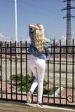 Een mooie jonge blonde vrouw bevindt zich met haar terug tegen de omheining stock fotografie