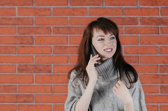 Een mooie jonge donkerbruine vrouw die door cellphone, gelukkig s spreken stock foto's