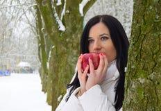 Een mooie jonge donkerbruine vrouw houdt een rode appel in haar handen Stock Afbeelding