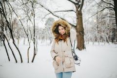 Een mooie jonge Kaukasische vrouw bevindt zich in een sneeuwpark in een jasje met een kap en bont op haar hoofd in jeans en houdt royalty-vrije stock foto
