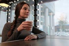 Een mooie jonge meisjeszitting alleen in een koffiewinkel Het meisje drinkt hete thee en zonnebaadt op een regenachtige de lented stock afbeeldingen