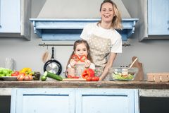 Een mooie jonge moeder en een dochter hebben pret terwijl het koken stock foto's