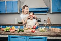 Een mooie jonge moeder en een dochter hebben pret terwijl het voorbereiden van hun maaltijd voor de blauwe keuken stock foto's