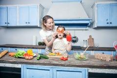 Een mooie jonge moeder en een dochter hebben pret terwijl het voorbereiden van hun maaltijd voor de blauwe keuken stock fotografie
