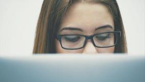 Een mooie jonge onderneemster die met een document in een tablet werken Langzame moties stock footage